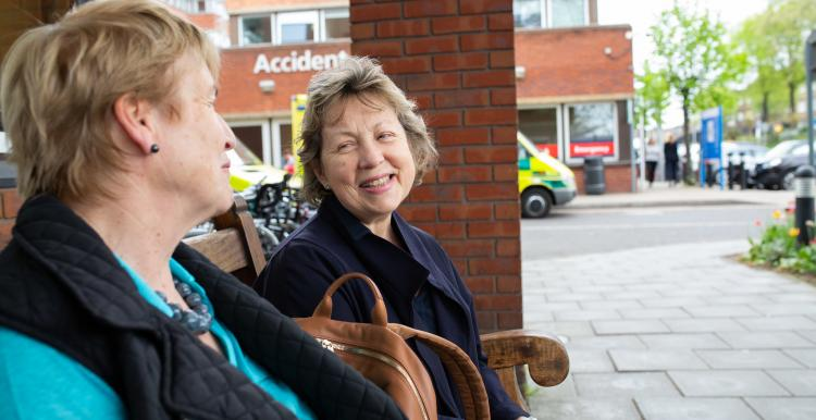 Two women sitting on a bench outside hospital talking