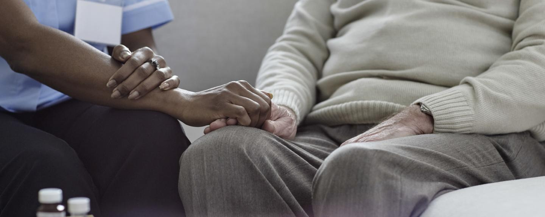 A nurse holding an old man's hand on the sofa.