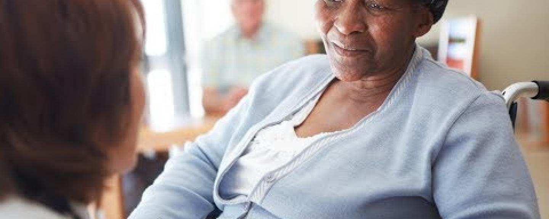 Black elderly woman ina nursing home being spoken to by a nurse