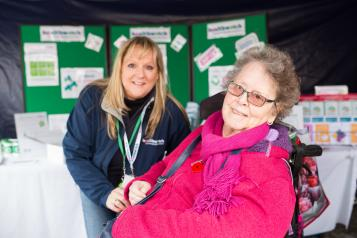 Healthwatch staff member at event talking to someone in a wheelchair