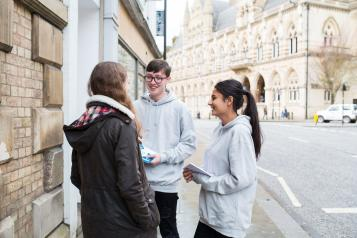 Two teenage Healthwatch volunteers talking to a member of the public about their experience
