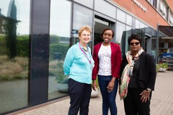 Three women outside hospital entrance