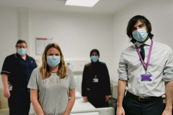 Four people wearing face masks inside the hospital