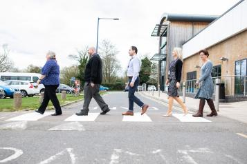 Staff members walking across a zebra crossing