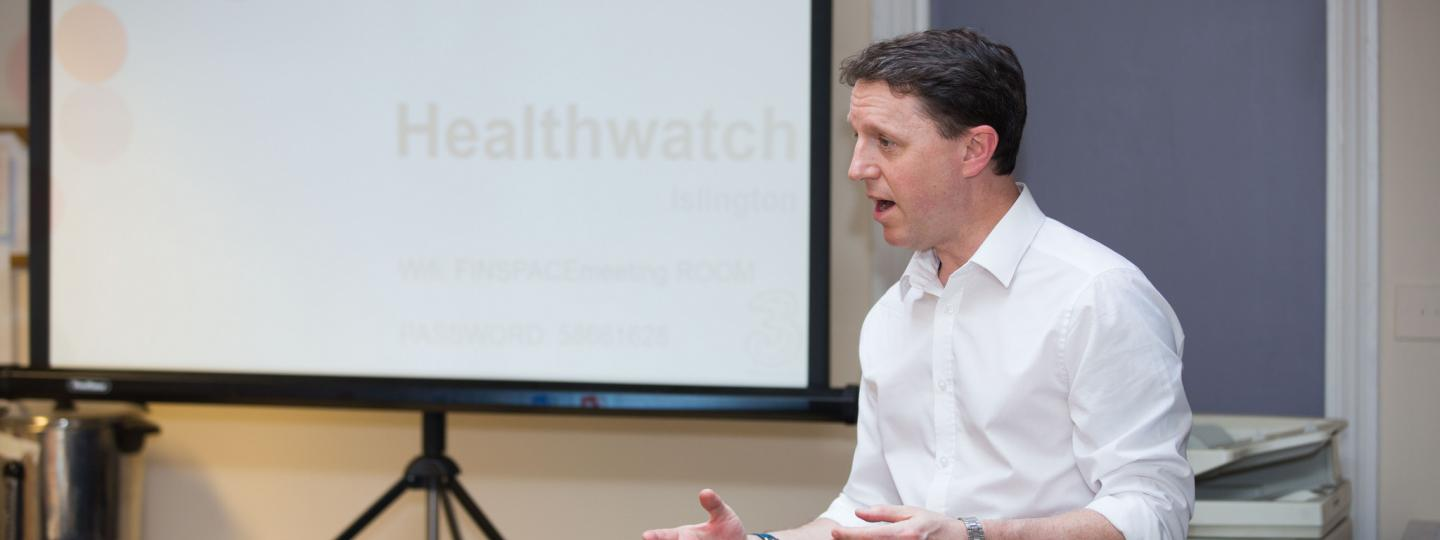 Image of a member of Healthwatch staff presenting at a meeting