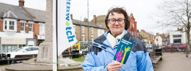 Female volunteer holding a leaflet