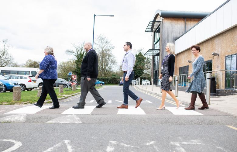 Staff members walking across a zebra crossing